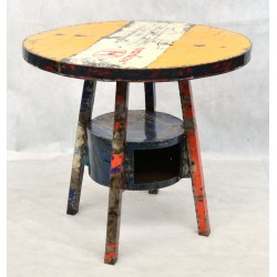 Round dining table with a low shelf between the four legs made from recycled oil drums